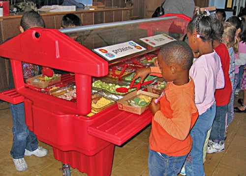 Children serving themselves from a healthy alternative salad bar at their school cafeteria
