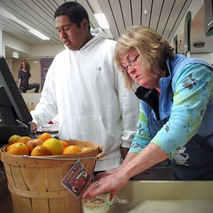 Harbor High School student Eric Lopez sells local produce in the student cafe