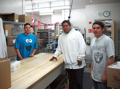 Harbor High School students George Juarez, Eric Lopez and Norberto Higaredo working in the school kitchen
