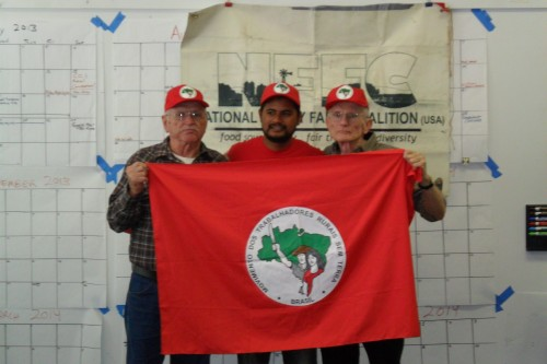 Larry, Flavio and Joe, with the flag of Brazil's Landless Worker's Movement (MST).